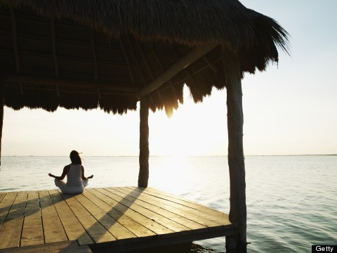 Woman practicing yoga with hair blowing in wind on dock