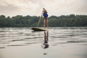 a young girl learning to paddle board
